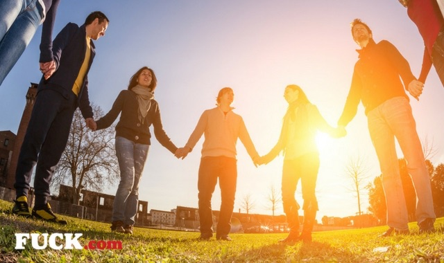 Group of people in a circle holding hands.  Fuck.com