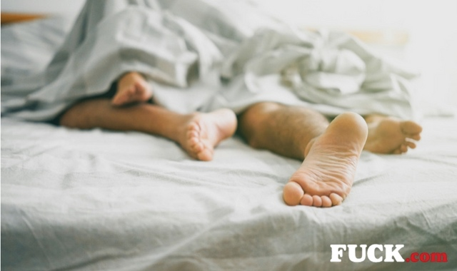 Two people lying in bed. Fuck.com.