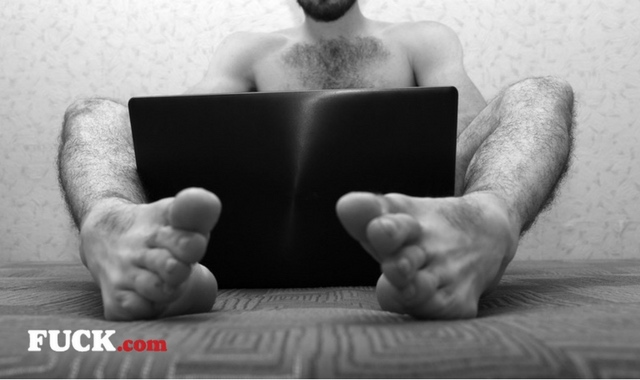 Naked man watching porn on laptop Fuck.com