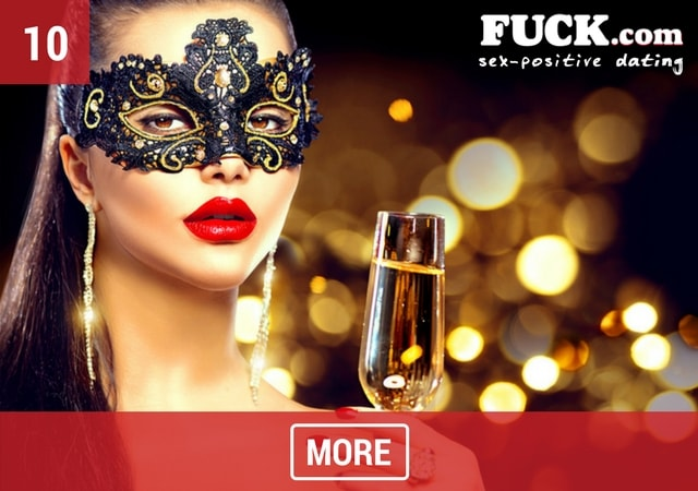 Sexy woman in a beautiful mask drinking champagne