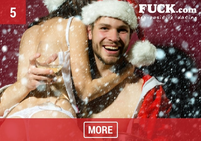 Sexy couple hugging in Santa Claus outfits with champagne