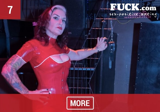 Sexy brunette dominatrix wearing red latex clothing